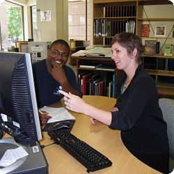 Librarian and student at a computer.